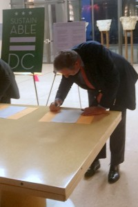 Ambassador Henne Schuwer signs the pledge to fulfill the goals that are part of Washington, D.C.'s sustainability plan.